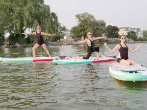 Kaitlyn Vittozzi, co-director of Finger Lakes Yogascapes, instructs stand-up paddleboard yoga, in addition to traditional yoga, in Canandaigua.