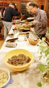 "One of the three long food tables at the November potluck dinner sponsored by Rochester Area Vegan Society. On the menu, among other things, were fresh salads including a kale salad tossed with a light peanut dressing and a wild rice salad filled with veggies, a vegan version of red beans and rice, California coleslaw and mac and ""cheese"" made with pureed squash."
