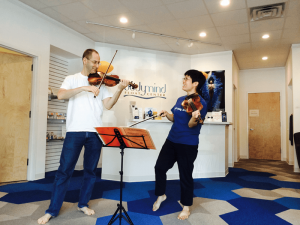 David Brinkman, founder and owner of Bodymind Float Center, and his, Pattie Sunwoo, paying violin at the float center.