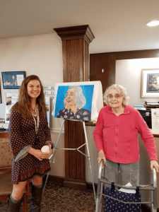 Students from Honeoye Central School next to residents at Quail Summit in Canandaigua whose portraits they painted as part of the school project.