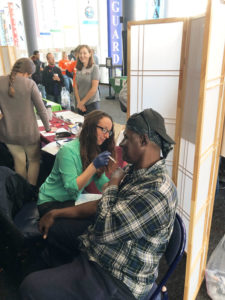 "Pharmacist Joy Snyder administering influenza vaccine to one of the attendees during ""Day of Services"" at Project Homeless Connect."