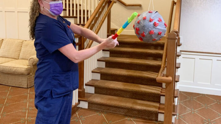 A Friendly Senior Living employee takes a swing at a COVID-19 pinata during a recent event at the facility.